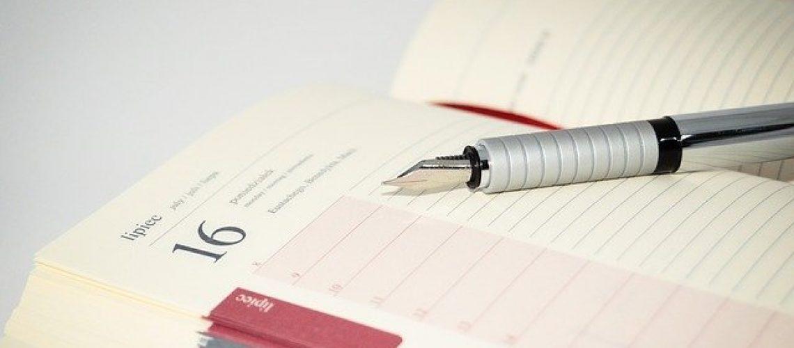 עט מונח על יומן ניהול ועד בית